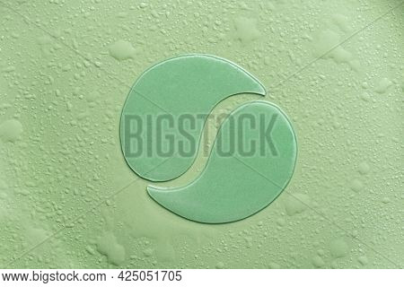 Hydrogel Green Eye Patches On Green Background With Water Drops Close Up. Cosmetic Moisturizing Unde