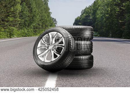 Summer Tires And Alloy Wheels Set On An Asphalt Road. Tire Change Season, Auto Trade, Copy Space, Au