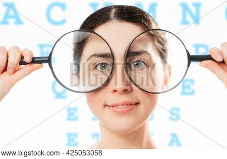 Ophthalmology. Portrait Of A Young Smiling Pretty Woman Holding Magnifying Glasses To Her Eyes. The