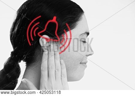 Tinnitus. A Dissatisfied Young Woman Holds Her Hand Over Her Ears, Experiencing Ringing And Pain. Th