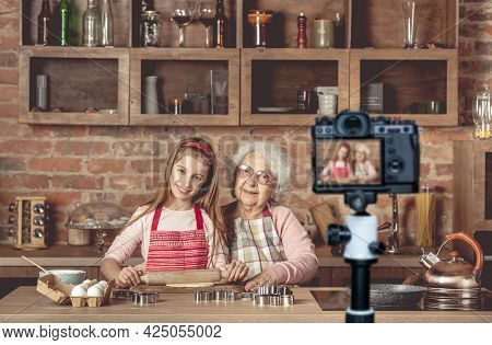 Eldery granny with her lovely granddaughter roll out the dough using the rolling pin and looking at camera. Blogger profession. Shooting with a camera for a blog