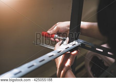 Do It Yourself Concept, Craftsmen Use C-shape Workpiece To Assemble Old Iron Parts. Make A Shelf On