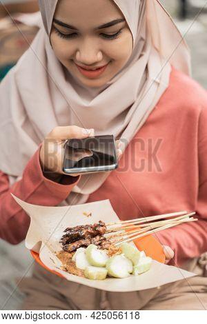 Chicken Satay Buyer Taking Photo Of Her Food Using Smart Phone