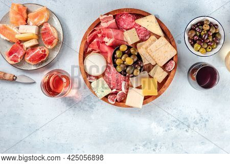 Buffet With Wine And Appetizers. Italian Delicatessen. A Platter Of Snacks With Salmon, Prosciutto,