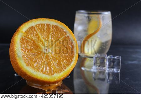 Lemonade With Orange And Ice In A Glass On A Black Background Next To Lies Ice And Orange. Summer Dr