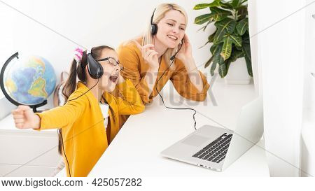 Mother And Her Girl Listening To Music On Laptop. They Sitting In Living Room. Natural Light Ambient