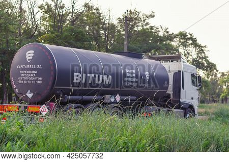Bitumen Tank Trailer Rides Along The Road Against The Backdrop Of The Morning Dawn Sky. Delivery And