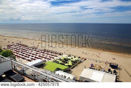 Latvia, Jurmala, June, 26, 2021 - People Enjoying Relaxing On The Baltic Sea Beach In Jurmala, Latvi