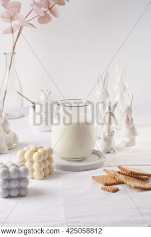 A Glass Of Milk On A Marble Plate On A White Table Cloth, Freshly Baked Cookies, Bubble Candles And