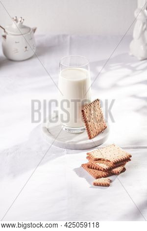 A Glass Of Milk On A Marble Plate On A White Table Cloth, Freshly Baked Cookies, And White Easter Bu