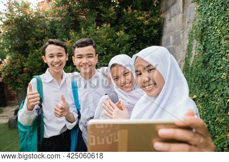 Four Teenagers In Junior High School Uniforms Taking Selfie Together Using A Smartphone