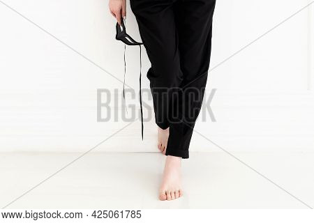 Close Up Legs With Bare Foot Of Young Woman In Black Pants Who Stands Near White Wall And Hold Black