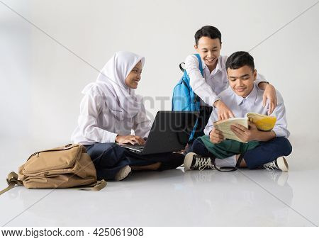 Smiling Three Teenagers In Junior High School Uniforms Sitting On The Floor Studying Together Using