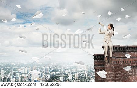 Young Woman Playing Trumpet And Sitting On Roof. Girl In White Business Suit With Music Brass Instru