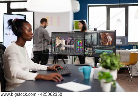 African Videographer Wearing Headset Editing Movie Using Post Production Software Working In Creativ