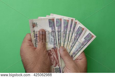 Egypt National Currency. Money Banknotes. Man Hands Hold Egyptian Pound Banknotes On Green Backgroun