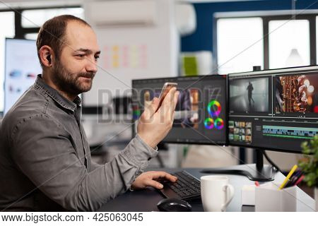 Video Editor Talking On Videocall With Client Holding Smartphone Editing Movie Sitting In Creative A