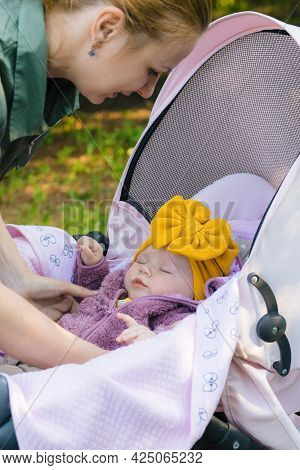 A Young Mother In A Khaki Dress, Smiling, Cradles Her Little Daughter In A Yellow Cap To Sleep In Na