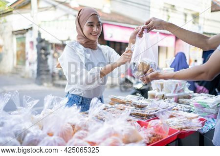 A Beautiful Girl In A Veil Buys Takjil Food From A Roadside Stall Seller