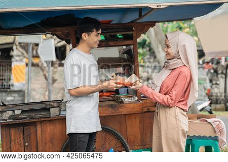 Muslim Woman Ordering Chicken Satay From Small Food Cart Seller.