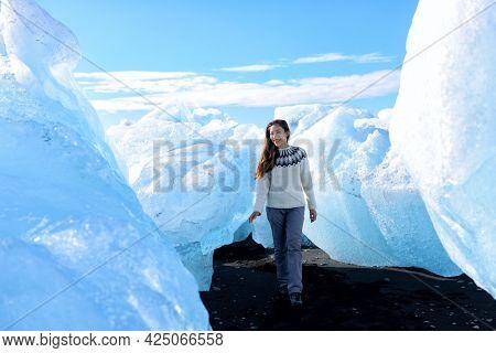 Iceland Amazing landscape at Iceberg beach. Tourist by icebergs on Ice beach, Breidamerkursandur aka Diamond Beach by jokulsarlon glacial lagoon glacier lake nature. Woman in icelandic sweater