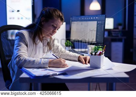 Overworked Woman Architect Checking And Matching Blueprints Sitting At Office Desk In Front Of Compu