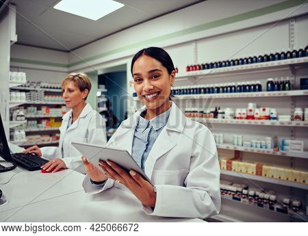 Portrait Of Smiling Young Female Pharmacist Wearing Labcoat Holding Digital Tablet With Senior Colle