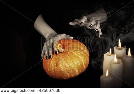 Witches Hands With Black Sharp Nails Keeps A Pumpkin Under A Candlelight In The Dark, Low Key, Selec