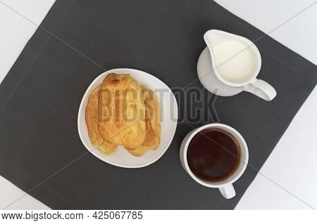 Profiteroles, Tea And Milk On Gray Background Top View. Puffs, Popovers, Eclaires