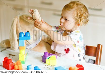 Adorable Toddler Girl With Favorite Plush Bunny Playing With Educational Toys In Nursery. Happy Heal