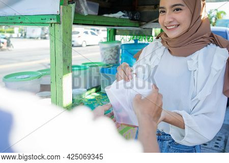 A Veiled Street Vendor Girl Delivers Es Campur Wrapped In A Plastic Bag To The Buyer