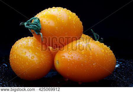 Beautiful Yellow Tomatoes On A Black Background.