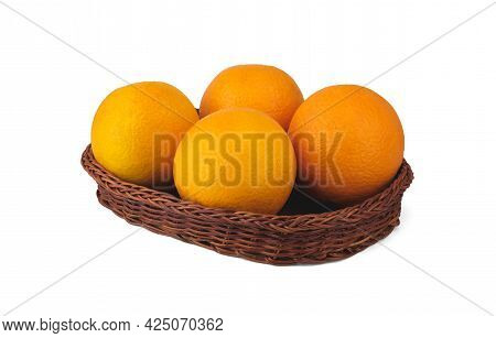 Four Large Oranges Lie In A Low Wicker Basket And Are Isolated On A Clean White Background With Some