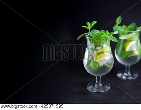 Mojito On A Black Background Banner. Summer Soft Drinks With Copy Space. Lemon, Lime, Mint, Ice, Wat