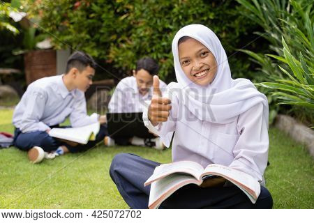 A Teenager In A Headscarf In School Uniform Smiles With A Thumbs Up While Sitting On The Grass