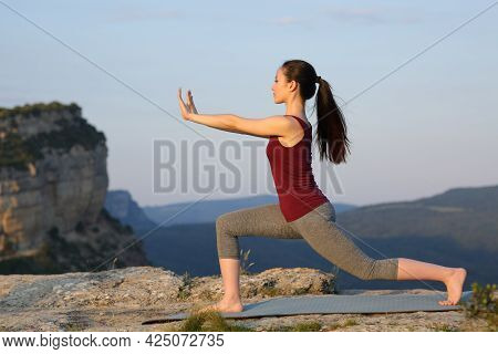 Side View Portrait Of An Asian Woman Practicing Tai Chi Exercise Outdoors In The Mountain Cliff