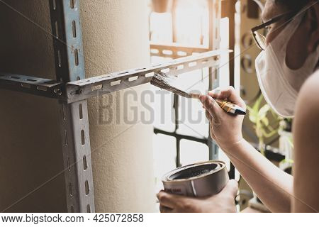 Do It Yourself Concept, Craftsmen Use Anti-rust Paint To Paint Old Iron Parts. Make A Shelf On Your