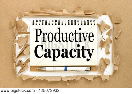 Productive Capacity. Text On Notepad Near Torn Paper