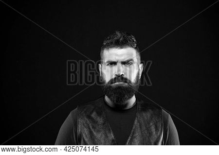 Man With Beard In Black Leather Clothes. Man Confident And Brutal Style Black Background. Barbershop