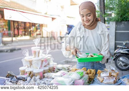 A Beautiful Girl In Veil Holding A Plastic Tray Chooses Various Types Of Fritters To Buy