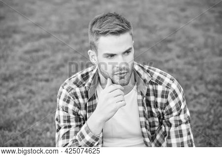 Never Too Young To Start Daily Skincare. Young Man Sit On Green Grass. Bachelor With Unshaven Face S