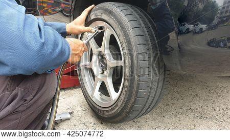 Bangkok,thailand-june 15,2021 : Male Auto Mechanic Inflate Car Tires At Wheel In Auto Repair Shop.ma
