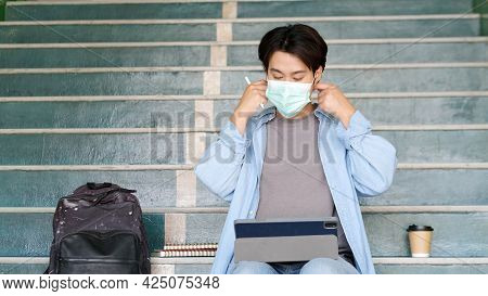 Young Asian Campus Student Man Wearing Protection Mask While Online Study In Campus, Coronavirus Pre