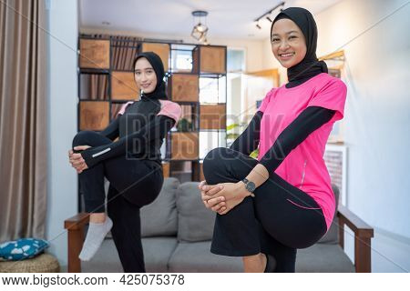 Two Women Wearing A Headscarf Smiling While Doing Lunges Movements While Exercising Indoors