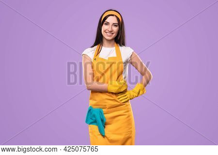 Happy Young Woman In Yellow Apron And Gloves With Duster Looking At Camera After Finishing Household