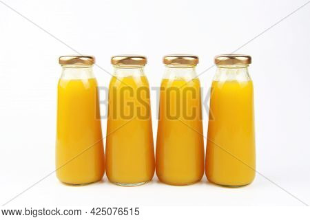 Fresh Fruit Juice In Small Glass Bottles On A White Background.empty Front Area For Branded Labels F