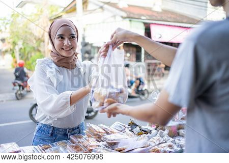 A Beautiful Girl In A Headscarf Takes A Takjil Food Order With A Plastic Bag