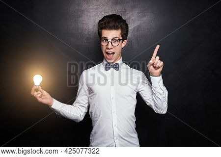 Funny Clever Young Man In White Shirt With Bow Tie And Nerdy Glasses Holding Glowing Light Bulb And