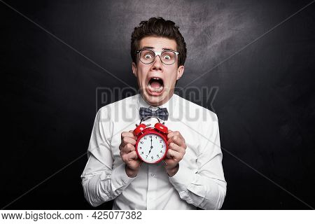 Young Nerdy Guy In Formal Outfit And Eyeglasses Showing Alarm Clock With 7 O Clock Time And Screamin
