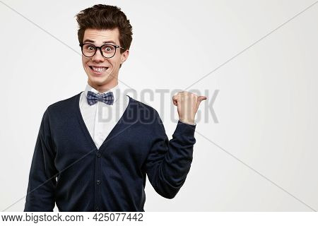 Funny Male Geek In Elegant Outfit And Glasses Smiling And Pointing Away On White Background In Studi